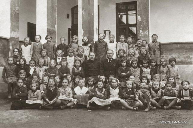Az eleki lányok 1938-1939 körüli első osztálya a templom melletti iskola udvarán.