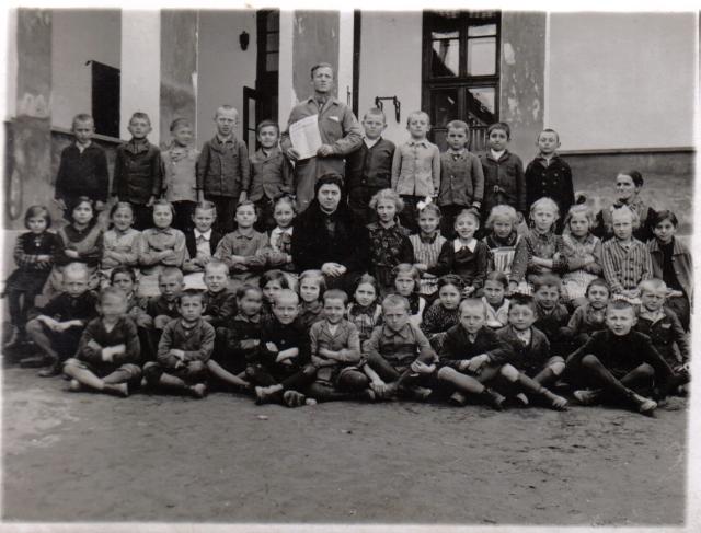Riha Ilona 2. osztályos diákjai körében 1941-ben, a templom melletti általános iskolában. Tőle balra a harmadik kislány Mag Valéria.